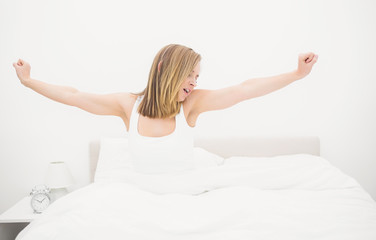 Sleepy woman yawning while stretching her arms in bed