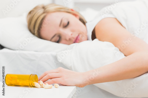Asleep woman with focus on spilt bottle of pills at home