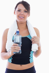 Portrait of woman in sportswear holding towel around neck and wa