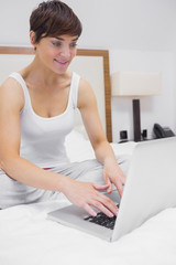 Happy woman using laptop in bed