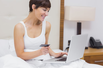 Woman shopping online in bed
