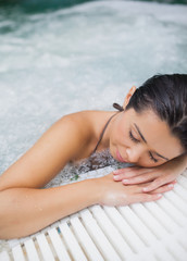 Woman resting at edge of jacuzzi