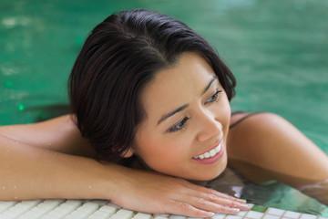 Attractive brunette relaxing in pool