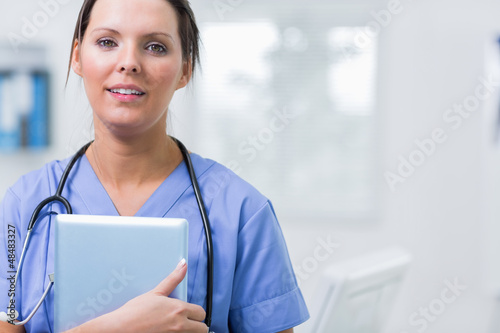 Female surgeon holding digital tablet at clinic