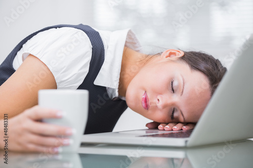 Business woman with coffee cup resting head on laptop at office