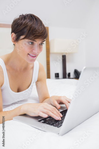 Pretty woman using laptop in bed