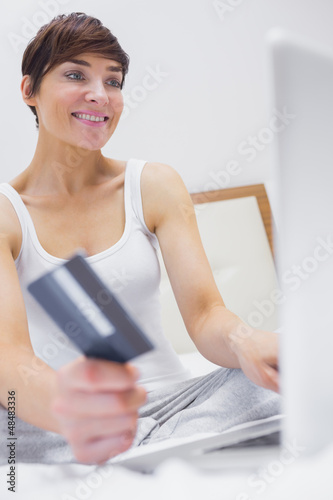 Woman shopping online in hotel room