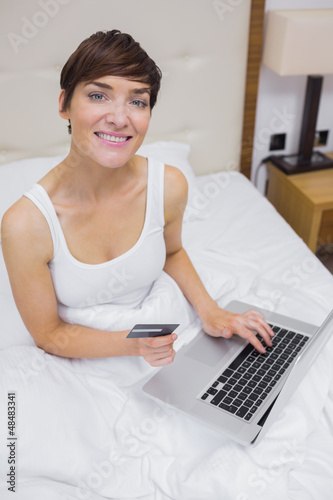 Smiling woman looking up from shopping online