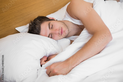 Handsome male sleeping in bed
