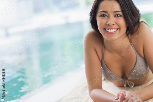 Smiling girl lying by swimming pool