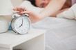 Sleepy woman in bed extending hand to alarm clock