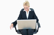 Happy business woman using laptop on chair