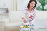 Woman with salad and laptop while pouring water in glass at home
