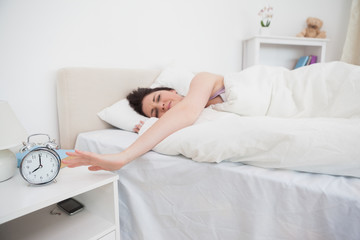 Sleepy woman extending hand to alarm clock