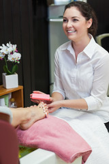 Woman buffering toe nails at spa center