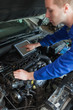 Mechanic with tablet pc repairing car