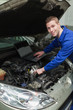 Happy mechanic with laptop repairing car