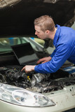 Repairman with laptop checking car engine