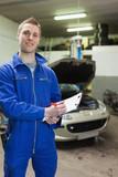 Happy auto mechanic writing on clipboard