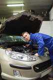 Auto mechanic examining car engine