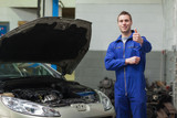 Mechanic by car giving thumbs up gesture