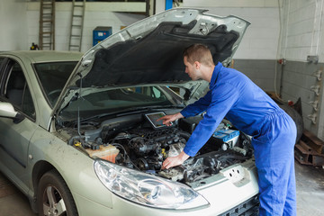 Mechanic examining car engine