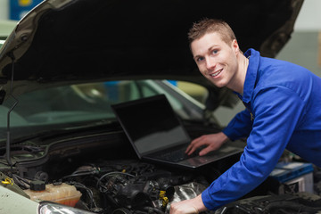 Happy mechanic using laptop