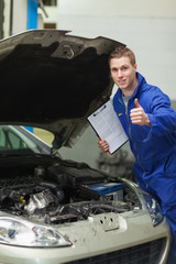 Mechanic by car showing thumbs up