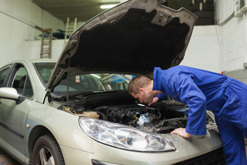 Mechanic working under car bonnet