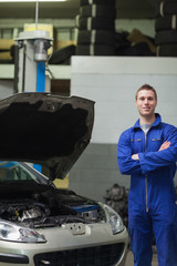 Happy mechanic standing by car with open hood