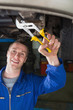 Mechanic repairing car with pliers