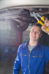 Happy male mechanic repairing car