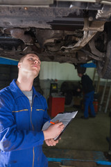Mechanic under car writing on clipboard