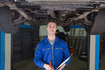 Mechanic with clipboard under car