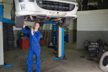 Mechanic working under raised car