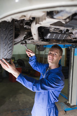 Confident mechanic repairing car