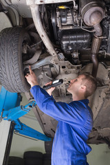 Auto mechanic examining under car