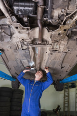 Auto mechanic examining car