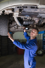 Male car mechanic examining vehicle