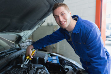 Male mechanic fixing car engine