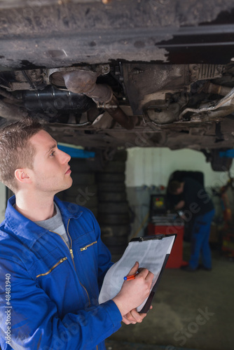 Mechanic with clipboard examining car