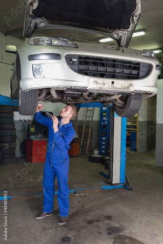 Mechanic working under raised car in garage