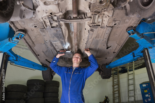 Mechanic inspecting under car