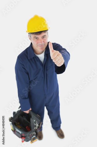 Mature man with tool bag showing thumbs up sign