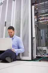Man working with his laptop on the floor beside servers