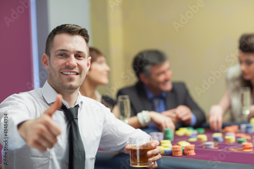 Man giving thumbs up and holding whiskey glass
