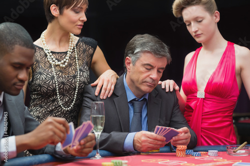Man playing poker with two women beside him