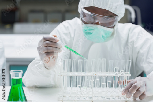 Chemist filling test tubes with green liquid