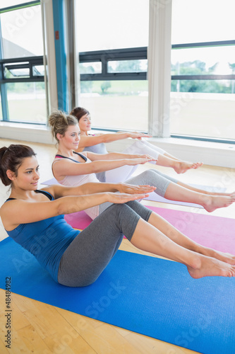 Women in boat pose at yoga class