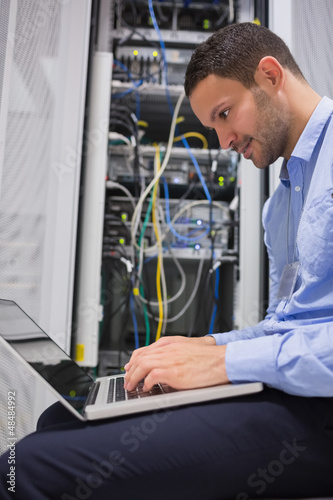 Man using laptop beside servers
